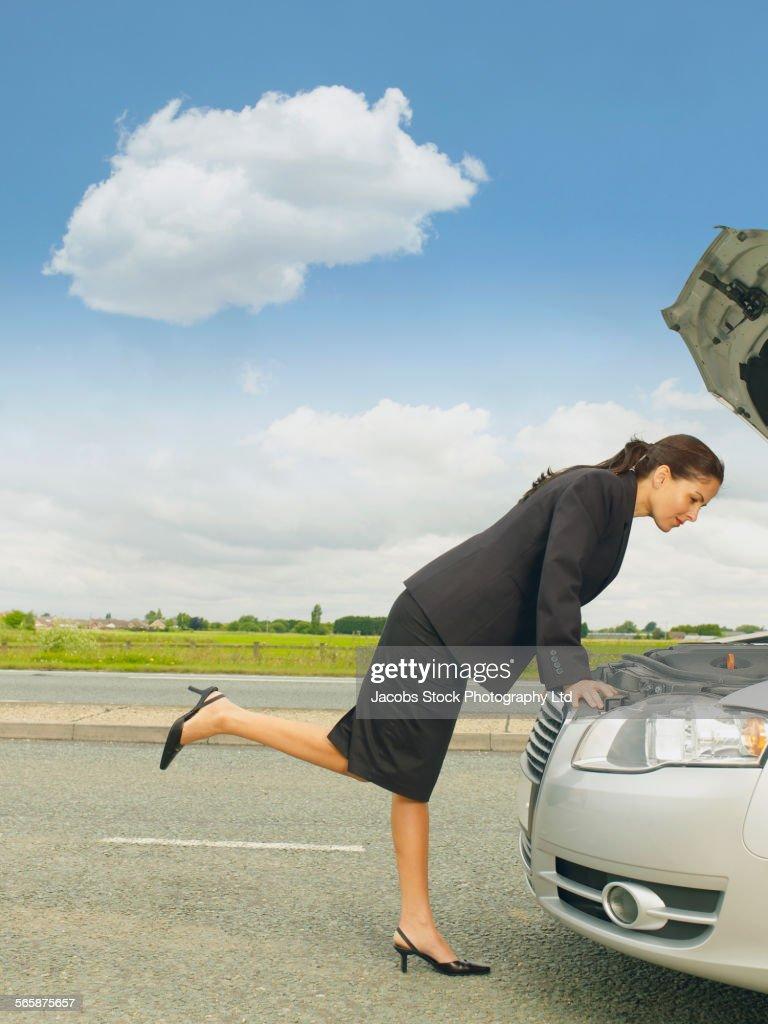 Caucasian businesswoman examining broken-down car engine on rural road : Stock Photo