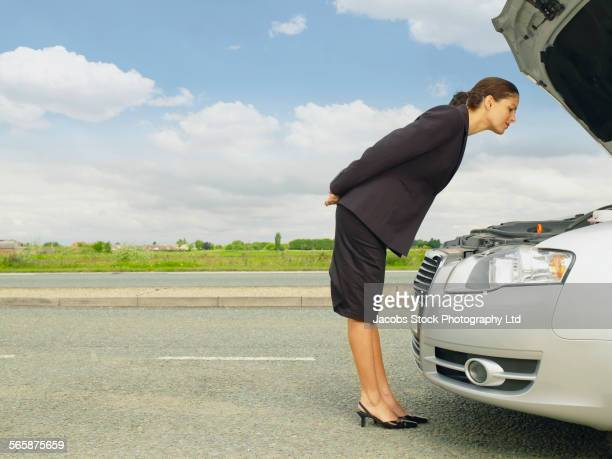 Caucasian businesswoman examining broken-down car engine on rural road