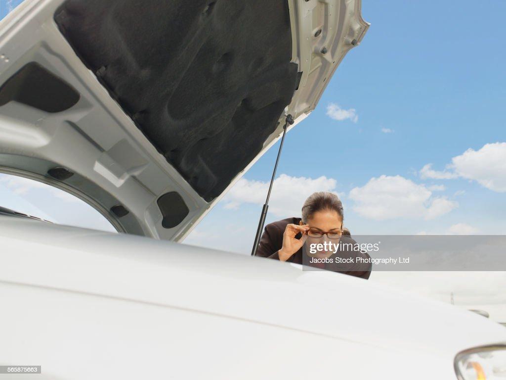 Caucasian businesswoman examining broken-down car engine under blue sky : Stock Photo