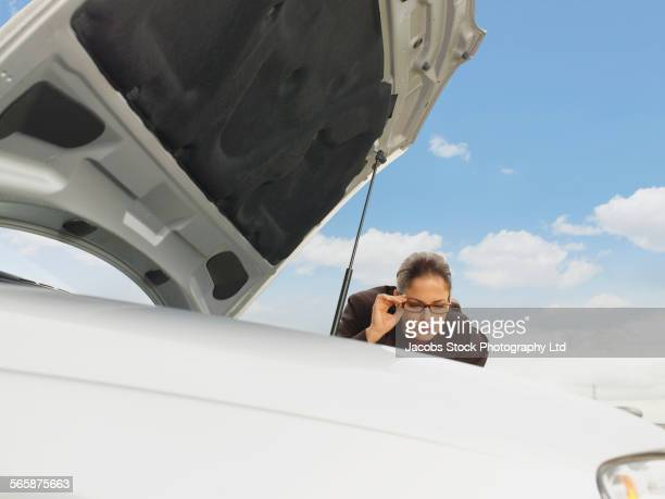 Caucasian businesswoman examining broken-down car engine under blue sky