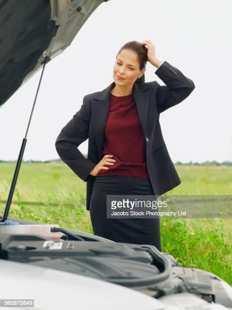 Caucasian businesswoman examining broken-down car on rural road