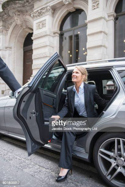 Caucasian businesswoman exiting car