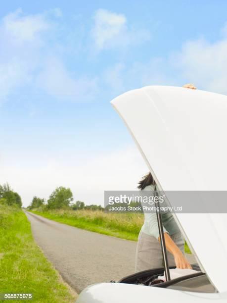 Caucasian businesswoman fixing broken down car on rural road