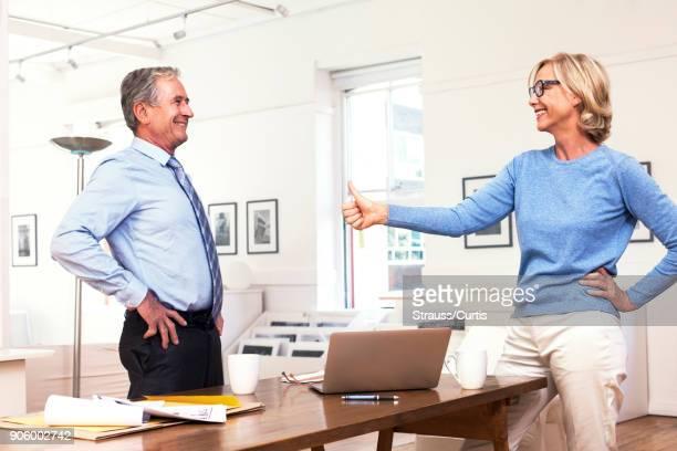 Caucasian businesswoman gesturing thumbs-up to businessman