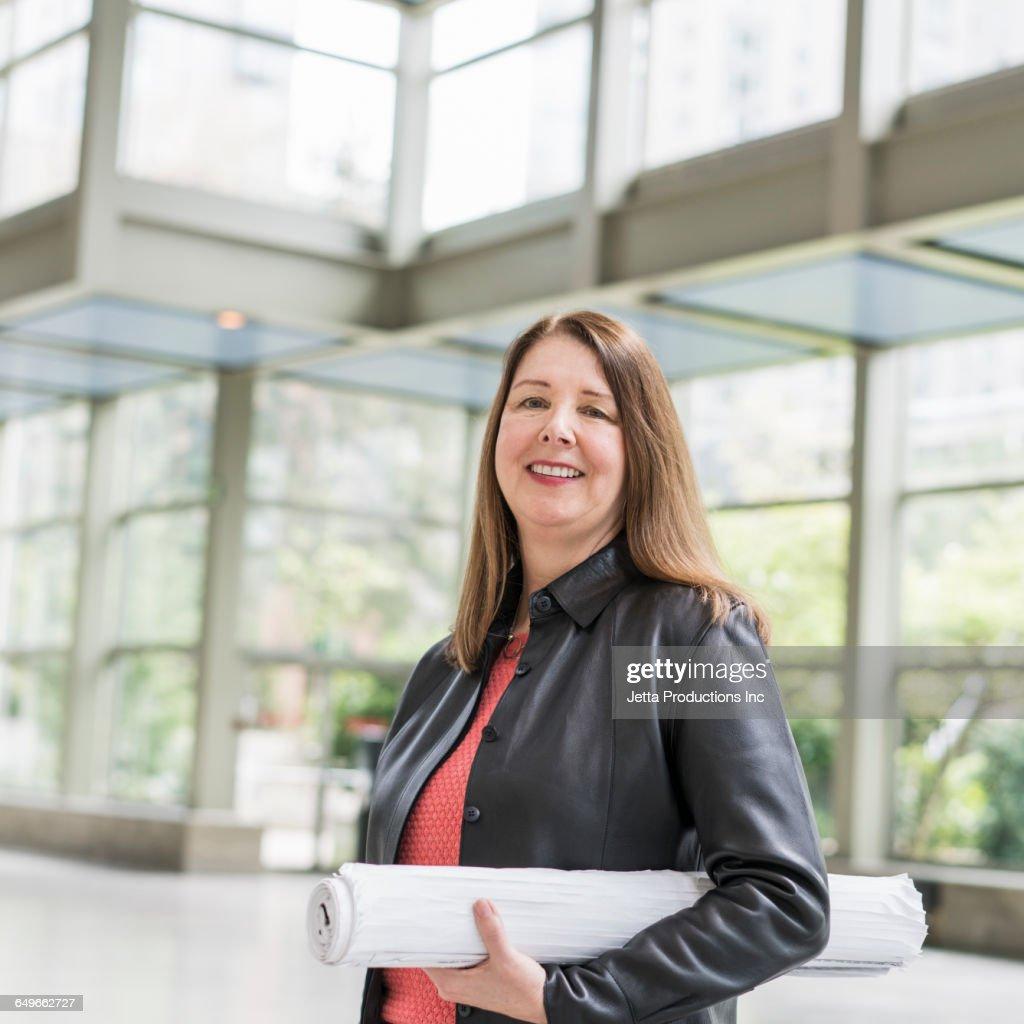 Caucasian businesswoman holding blueprints in office : Stock Photo