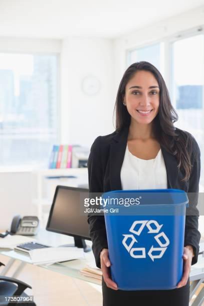 Caucasian businesswoman holding recycle bin