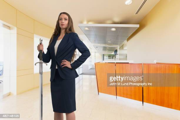 caucasian businesswoman holding sword in office - sword stock pictures, royalty-free photos & images