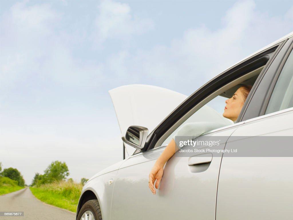 Caucasian businesswoman in broken down car on rural road : Stock Photo