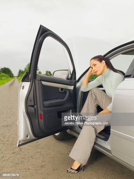Caucasian businesswoman in broken down car on rural road