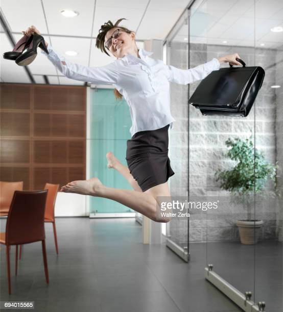 Caucasian businesswoman jumping in office