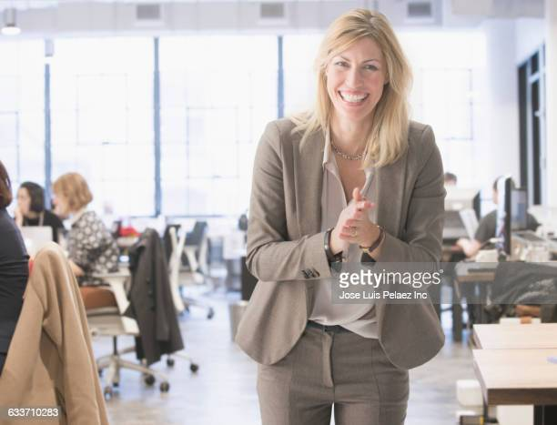 caucasian businesswoman laughing in office - incidental people stock pictures, royalty-free photos & images
