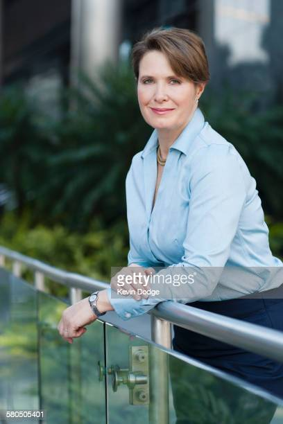 Caucasian businesswoman leaning on banister outdoors