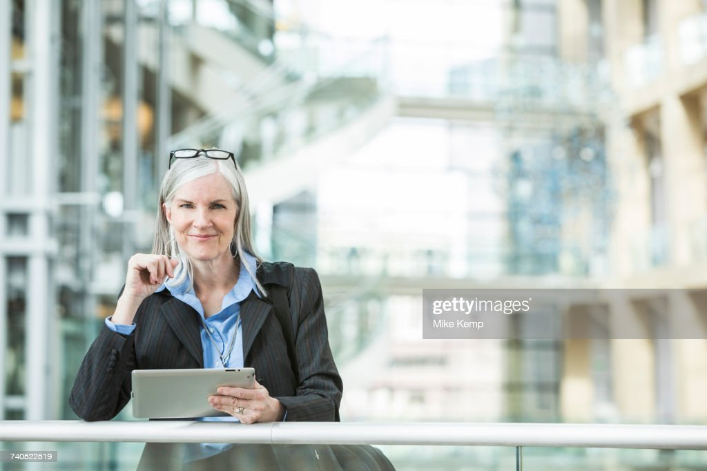 caucasian businesswoman leaning on railing in lobby using digital