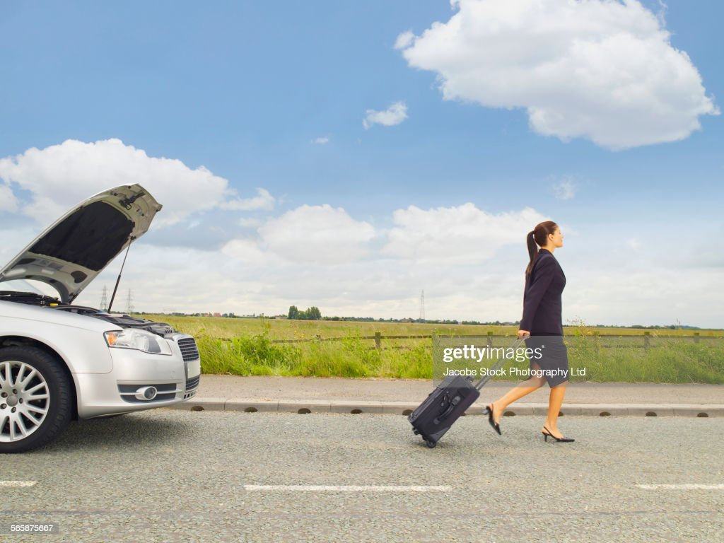 Caucasian businesswoman leaving broken down car on rural road : Stock Photo
