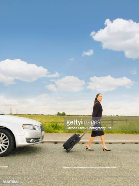 Caucasian businesswoman leaving broken down car on rural road