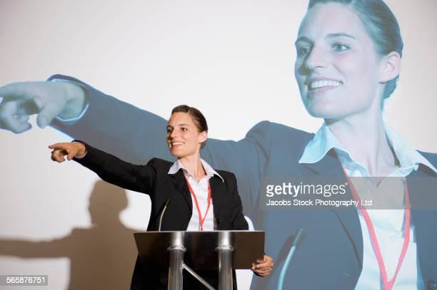 Caucasian businesswoman pointing from podium