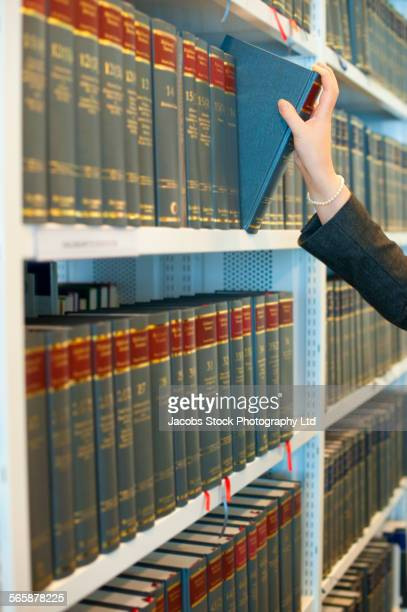 Caucasian businesswoman pulling book from law library shelf