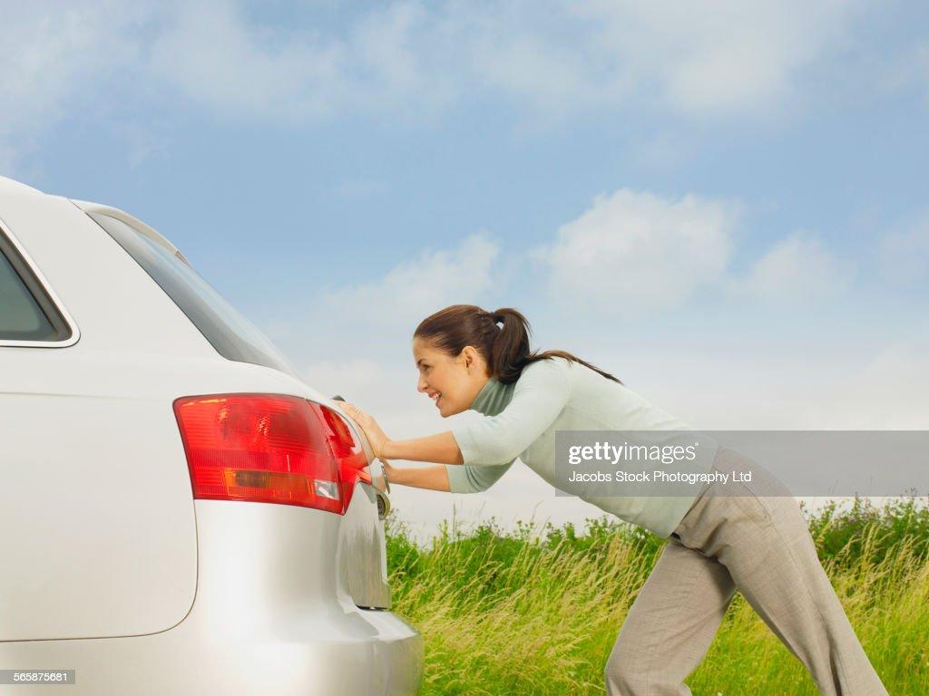 Caucasian businesswoman pushing broken down car on rural road : Stock Photo