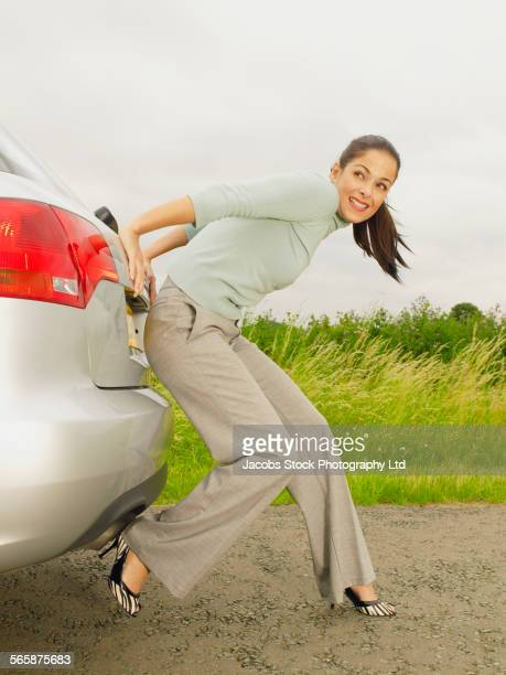 Caucasian businesswoman pushing broken down car on rural road