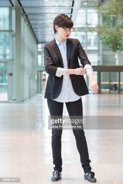 Caucasian businesswoman rolling her sleeves in office lobby