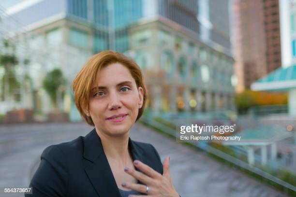 Caucasian businesswoman sitting in city park