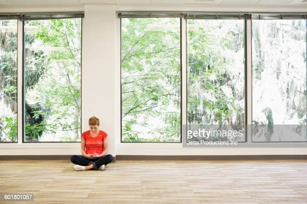 Caucasian businesswoman sitting in empty office