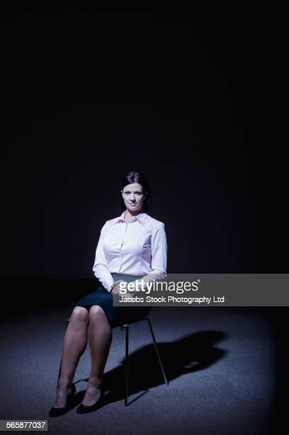 Caucasian businesswoman sitting in spotlight