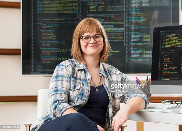 Caucasian businesswoman smiling at computer