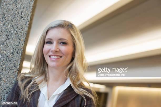 Caucasian businesswoman smiling in lobby