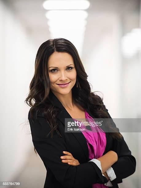 Caucasian businesswoman smiling in office corridor