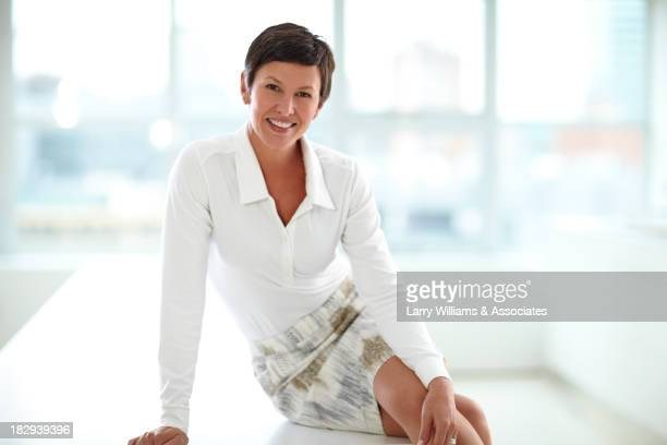 caucasian businesswoman smiling in office - older women in short skirts stock pictures, royalty-free photos & images