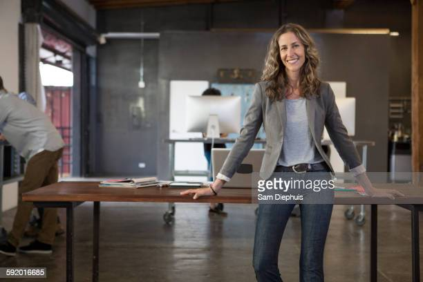 caucasian businesswoman smiling in office - incidental people stock pictures, royalty-free photos & images