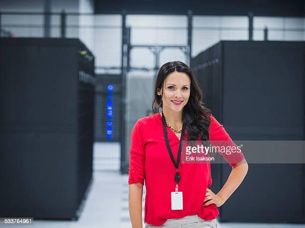 caucasian businesswoman smiling in server room - ストラップ ストックフォトと画像