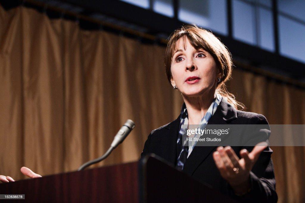 Caucasian businesswoman speaking at podium : Stock Photo
