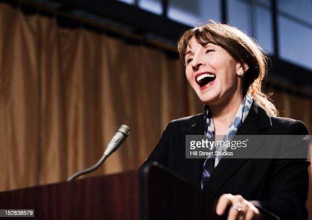 caucasian businesswoman speaking at podium - politica foto e immagini stock