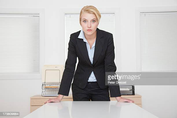 Caucasian businesswoman standing at desk in office