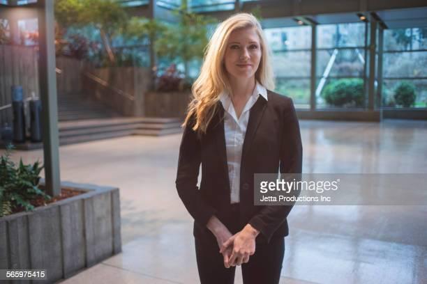 Caucasian businesswoman standing in office lobby
