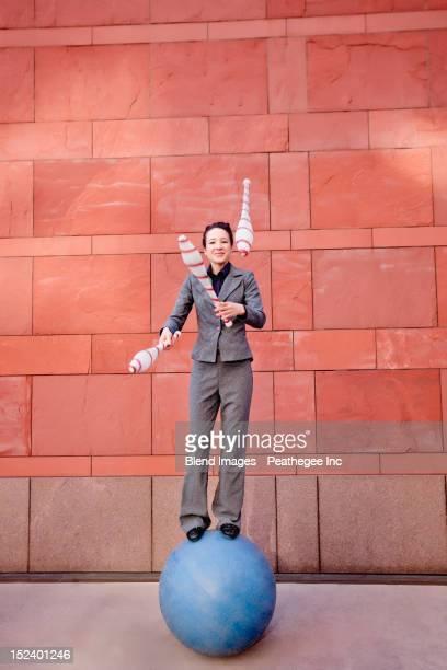 Caucasian businesswoman standing on ball juggling