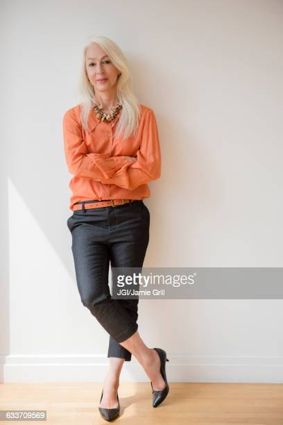 Caucasian businesswoman standing with arms crossed