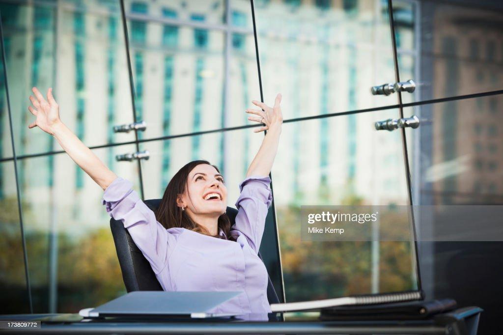 Caucasian businesswoman stretching at desk : Stock Photo