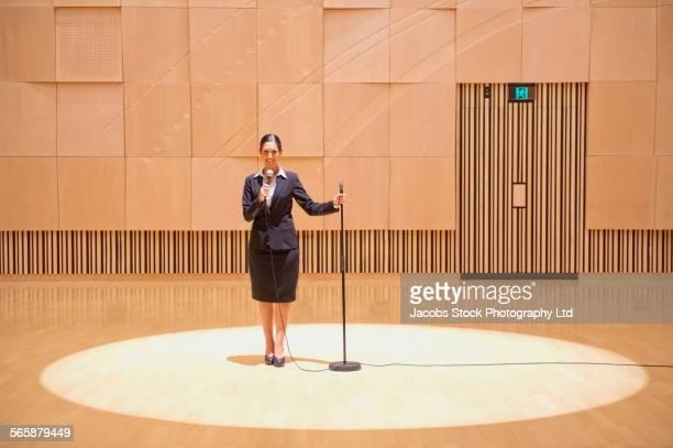 Caucasian businesswoman talking into microphone in spotlight