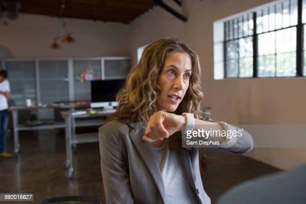 Caucasian businesswoman talking into smart watch in office