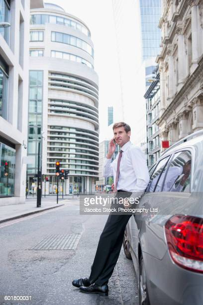 Caucasian businesswoman talking on cell phone at car