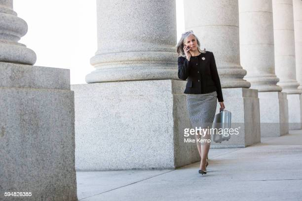 Caucasian businesswoman talking on cell phone under columns