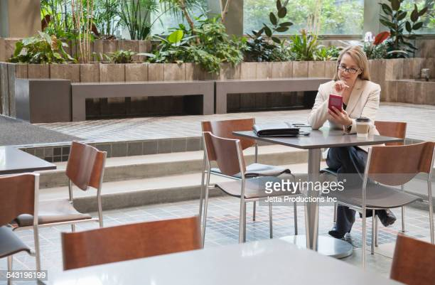 Caucasian businesswoman using cell phone at table