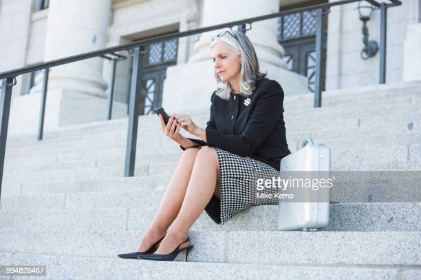 Caucasian businesswoman using cell phone on courthouse steps