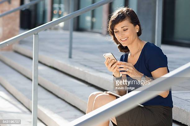 Caucasian businesswoman using cell phone on staircase