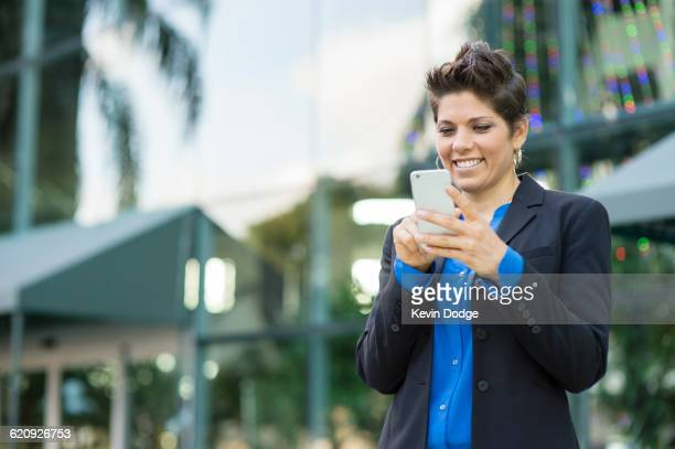 Caucasian businesswoman using cell phone outdoors