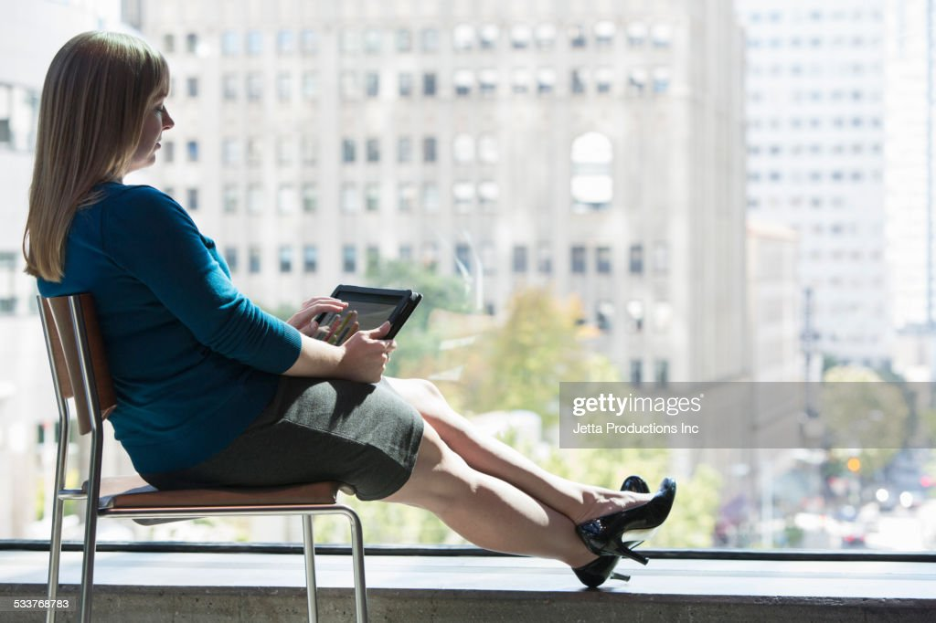Caucasian businesswoman using digital tablet at office window : Foto stock