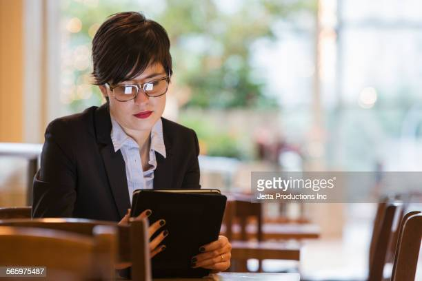 Caucasian businesswoman using digital tablet at table
